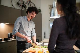 Hombre cocinando mientras su esposa mira