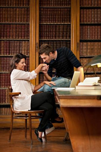 Estudiantes siendo románticos en la biblioteca