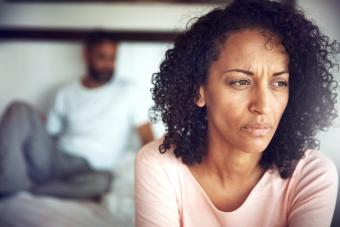 Mujer enfadada mirando al infinito con su marido desenfocado por detrás