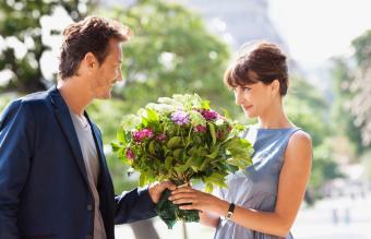 Hombre dando un ramo de flores a una mujer