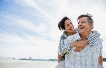 Hombre que se ríe y le lleva a su esposa a la playa